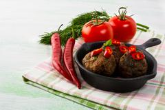 Grilled meatballs served with chili pepper slices in cast iron skillet - stock photo