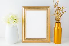 Gold frame mockup with golden vase and ivory hydrangea - stock photo