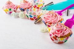 Pink birthday cupcakes  and cookware background Stock Photos