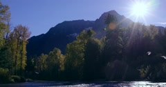 A Bella Coola river flows, with trees and mountains in the background. Sun Stock Footage