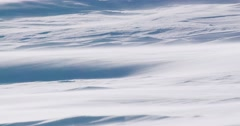 Close up shot to snow blowing across a plain zooms out to a wide shot with Stock Footage