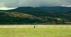 Wide shot of spinkle systems watering a field in Bella Coola, BC. Stock Footage