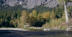 A boat paddles down a river past a wildlife viewing station in Bella Coola. Stock Footage
