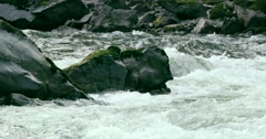 A close up shot of a river in Bella Coola as the water rushes through the rocks. - stock footage