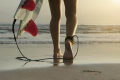 Female surfer feet with board walking to ocean Stock Photos