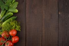 Tomatoes, cucumbers, dill and horseradish leaves on the old wooden background Stock Photos