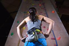 Japanese climbing athlete getting ready to climb gym wall - stock photo