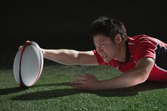 Portrait of Japanese rugby player diving to score a try Stock Photos
