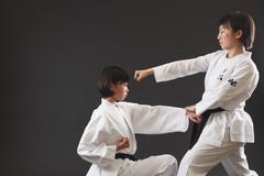 Japanese kids in karate uniform on black background Stock Photos