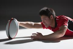 Portrait of Japanese rugby player diving to score a try - stock photo