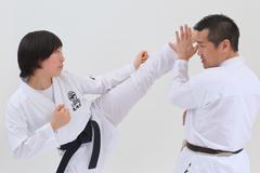 Japanese kid in karate uniform training with teacher on white background - stock photo