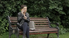 YOUNG GIRL HANG UP PHONE SITTING ON A PARK BENCH Stock Footage