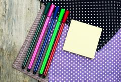 Color pencils and pen on wooden table see on top view. Stock Photos