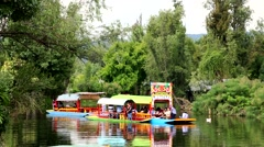 Tourists enjoy the gondola ride at the Xochimilco canals. Stock Footage