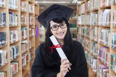 Cheerful bachelor with certificate in library Stock Photos