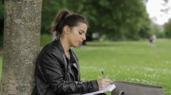 GIRL WRITES DOWN IDEAS/WORKS Stock Footage