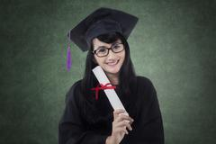 Happy bachelor holds diploma in class Stock Photos