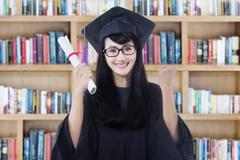 Happy bachelor with mortarboard in library - stock photo
