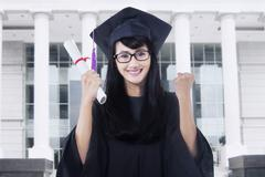 Happy student with mortarboard in campus Stock Photos