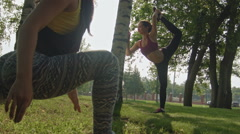 Young attractive sport women doing stretching fitness exercises in the park Stock Footage