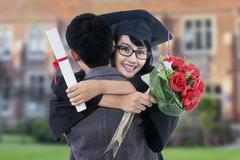 Student with mortarboard hugs her boyfriend Stock Photos