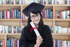 Young bachelor with certificate in library - stock photo