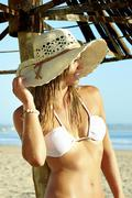 Sexy young woman in white bikini top and hat on beach Stock Photos
