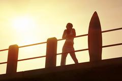 Silhouette of sexy female surfer standing with board on pier Stock Photos
