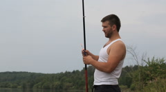 Young man configures the his fishing rod Stock Footage