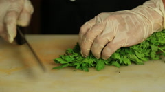 Close up of the hands of a chef chopping parsley - stock footage