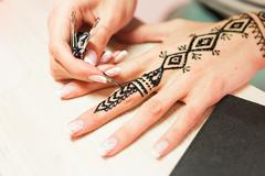 Young woman mehendi artist painting henna on the hand Stock Photos