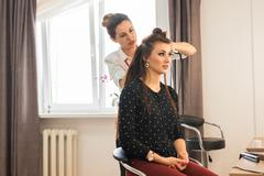 Hairdresser doing hair style for woman. Concept of fashion and beauty Stock Photos