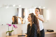 Hairdresser doing hair style for woman. Concept of fashion and beauty - stock photo