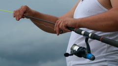 Young fisherman configures the his fishing rod Stock Footage