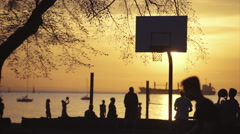 Slow motion lockdown shot of people playing basketball by water during sunset Stock Footage