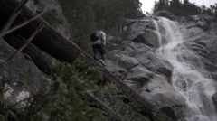 Low angle tracking shot of man walking on log towards waterfall, Squamish, Stock Footage