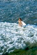 Female surfer walking out into ocean. Arial view Stock Photos