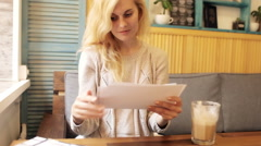 Girl Looking Photos Sitting in Cafe Stock Footage