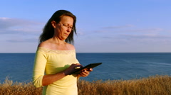 4K. Mature adult Woman in yellow blouse  near  sea coast with tablet Stock Footage