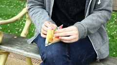 Young adult woman seated in park opening sliced apple pack Stock Footage