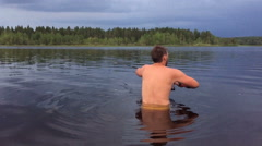 young man is fishing in the water up to his waist - stock footage