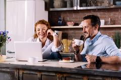 Couple looking at laptop while having breakfast Stock Photos