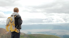 Hiker looking at view in high altitude mountain above the clouds Stock Footage