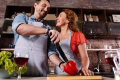 Man cutting paprika and talking to wife - stock photo