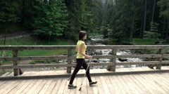 Young, beautiful woman hiking in the bridge in the forest, super slow motion Stock Footage