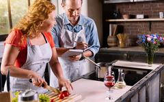 Woman dictating ingredients to man Stock Photos