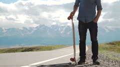 Bearded tattooed man in a red shirt posing with a longboard Stock Footage