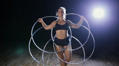Art gymnastics. Woman rotate ball from many hula hoop on scene. Stock Footage