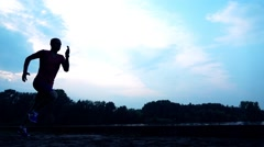Silhouette of athletic man running on sandy riverside in the evening, 240 fps Stock Footage