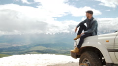Happy Traveler man sitting on his car on mountains top. 4x4 travel trekking Stock Footage